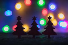 圣诞节弄脏了剪影冷杉木有诗歌选光背景,选择聚焦 库存照片