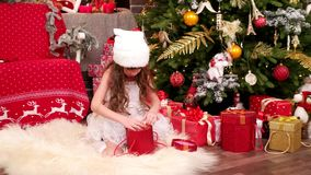 圣诞节惊奇, A儿童游戏在的圣诞前夕,有看礼物,儿童狂欢节的兴趣的小女孩房子里 股票录像