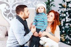圣诞节愉快的三口之家人和杉树与礼物盒在白色卧室背景 免版税图库摄影
