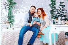 圣诞节愉快的三口之家人和杉树与礼物盒在白色卧室背景 免版税库存照片