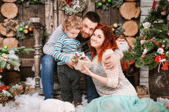 圣诞节愉快的三口之家人和杉树与礼物盒新年冬天装饰了背景 库存照片