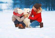 圣诞节愉快的微笑的家庭、母亲和走与在雪的白色萨莫耶特人狗的儿子孩子在冬天da 库存照片