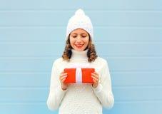 圣诞节愉快的微笑的少妇在穿在蓝色的手上拿着礼物盒一件被编织的帽子毛线衣 库存照片