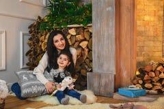 圣诞节愉快的微笑的母亲家庭画象坐地板近对用冷杉和诗歌选装饰的壁炉 库存图片