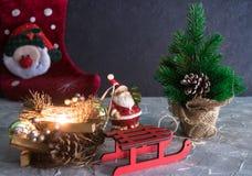 圣诞节愉快的快活的新年度 圣诞老人玩具、一个灼烧的蜡烛和雪橇 圣诞节节假日 套圣诞节ornam 库存照片