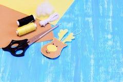 圣诞节感觉鹿装饰品,剪刀,螺纹,针,绳子,补白,在蓝色木背景的毛毡板料 免版税图库摄影