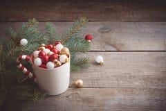圣诞节戏弄在一个杯子的球在木背景 免版税图库摄影