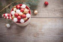 圣诞节戏弄在一个杯子的球在木背景 免版税库存照片