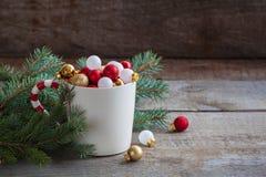 圣诞节戏弄在一个杯子的球在木背景 库存照片