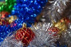 圣诞节戏弄在闪亮金属片,蓝色,银色和绿色的金黄和红颜色 库存照片