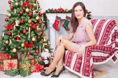 圣诞节或新年庆祝 一件欢乐礼服的少妇在圣诞节内部的一把椅子坐,在壁炉附近, Chr 库存图片