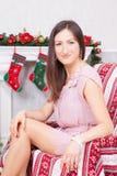 圣诞节或新年庆祝 一件欢乐礼服的少妇在圣诞节内部的一把椅子坐,在壁炉附近, Chr 免版税库存图片