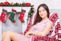 圣诞节或新年庆祝 一件欢乐礼服的少妇在圣诞节内部的一把椅子坐,在壁炉附近, Chr 图库摄影