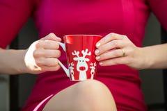 圣诞节或新年庆祝 一件红色礼服的妇女保留有鹿的圣诞节杯子 特写镜头 免版税库存照片
