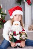 圣诞节或新年庆祝 圣诞老人帽子的小逗人喜爱的女孩在头拥抱玩具圣诞老人并且在圣诞节tr附近坐 库存图片
