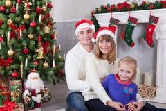 圣诞节或新年庆祝 坐在与xmas礼物的圣诞树附近的愉快的年轻家庭 与圣诞节stoc的一个壁炉 图库摄影