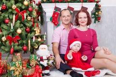 圣诞节或新年庆祝 坐在与xmas礼物的圣诞树附近的愉快的年轻家庭 与圣诞节stoc的一个壁炉 免版税库存图片