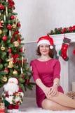圣诞节或新年庆祝 坐在与xmas礼物的圣诞树附近的红色礼服的愉快的妇女 与christma的一个壁炉 库存照片