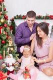 圣诞节或新年庆祝 坐在椅子的愉快的年轻家庭在与xmas礼物的圣诞树附近 与克里斯的一个壁炉 免版税库存图片