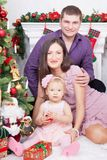 圣诞节或新年庆祝 坐在椅子的愉快的年轻家庭在与xmas礼物的圣诞树附近 与克里斯的一个壁炉 库存图片