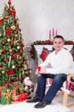 圣诞节或新年庆祝 年轻人在扶手椅子坐并且在与xmas礼物的圣诞树附近拿着杯子 壁炉w 库存图片
