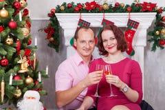 圣诞节或新年庆祝 年轻美好的加上香槟坐在与xmas礼物的圣诞树附近的一杯 A 图库摄影
