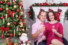 圣诞节或新年庆祝 年轻美好的加上香槟坐在与xmas礼物的圣诞树附近的一杯 A 库存图片