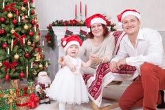 圣诞节或新年庆祝 快乐的年轻三口之家画象在圣诞树附近的人与xmas礼物 fi 库存图片