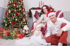 圣诞节或新年庆祝 快乐的年轻三口之家画象在圣诞树附近的人与xmas礼物 fi 免版税库存照片