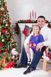 圣诞节或新年庆祝 愉快的坐在椅子的父亲和女儿在与xmas礼物的圣诞树附近 壁炉机智 库存照片