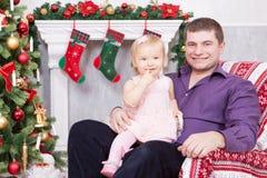圣诞节或新年庆祝 愉快的坐在椅子的父亲和女儿在与xmas礼物的圣诞树附近 壁炉机智 库存图片