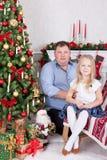 圣诞节或新年庆祝 愉快的坐在椅子的父亲和女儿在与xmas礼物的圣诞树附近 壁炉机智 免版税库存图片