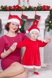 圣诞节或新年庆祝 愉快的母亲和女儿坐在圣诞树附近的红色圣诞老人帽子的与xmas礼物 一firep 免版税库存图片
