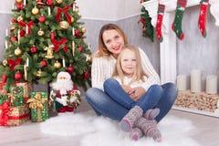 圣诞节或新年庆祝 有坐在与xmas礼物的圣诞树附近的女儿容忍的愉快的年轻母亲 一棵冷杉 库存照片