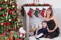 圣诞节或新年庆祝 有她的女儿的愉快的母亲在一个白色壁炉附近坐在圣诞树旁边 免版税库存图片