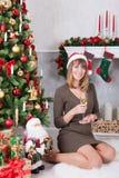 圣诞节或新年庆祝 有香槟坐在与xmas礼物的圣诞树附近的一杯的愉快的妇女 一个壁炉 免版税库存图片