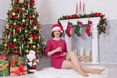 圣诞节或新年庆祝 有香槟坐在与xmas礼物的圣诞树附近的一杯的愉快的妇女 一个壁炉 库存图片