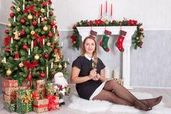 圣诞节或新年庆祝 有香槟坐在与xmas礼物的圣诞树附近的一杯的愉快的妇女 一个壁炉 免版税库存照片
