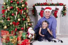 圣诞节或新年庆祝 父亲和女儿在圣诞树附近坐 父亲有在他的头的一个圣诞老人帽子 F. stratocaster电吉他 免版税库存图片