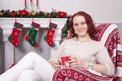 圣诞节或新年庆祝 白色被编织的套头衫的少妇拿着一个杯子手中和坐在圣诞节的一把椅子 库存照片