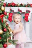 圣诞节或新年庆祝 逗人喜爱的桃红色礼服的小女孩在家装饰圣诞树的在与基督的壁炉附近 免版税库存图片