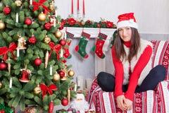 圣诞节或新年庆祝 一个红色套头衫、毛皮背心和圣诞老人帽子的少妇,在圣诞节内部的一把椅子坐, 库存照片