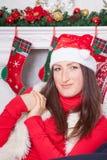 圣诞节或新年庆祝 一个红色套头衫、毛皮背心和圣诞老人帽子的少妇,在圣诞节内部的一把椅子坐, 图库摄影