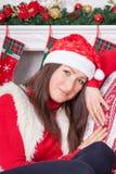 圣诞节或新年庆祝 一个红色套头衫、毛皮背心和圣诞老人帽子的少妇,在圣诞节内部的一把椅子坐, 免版税库存图片