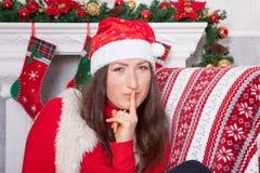 圣诞节或新年庆祝 一个红色套头衫、毛皮背心和圣诞老人帽子的少妇,在圣诞节内部的一把椅子坐, 库存图片