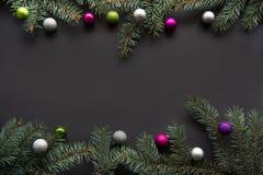 圣诞节或新年装饰背景:冷杉木分支,在黑背景的五颜六色的玻璃球与拷贝空间 顶视图 免版税库存图片