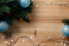 圣诞节或新年装饰背景:毛皮树分支,在木背景的五颜六色的玻璃球 免版税库存图片