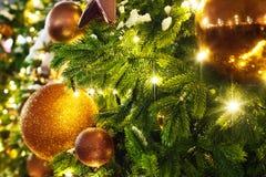 圣诞节或新年贺卡、金黄圣诞装饰玻璃球在绿色杉木分支,白雪和发光的光 库存照片