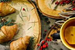 圣诞节或新年酥皮点心,与一份温暖的饮料的新月形面包,茶用柠檬 寒假概念 节假日 库存照片