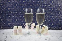 圣诞节或新年食物和饮料使用蛋白软糖的摄影图象塑造了作为在雪的雪人与杯香槟 免版税库存图片